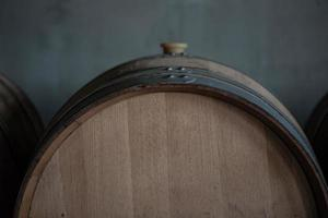 Wine barrels stacked in cellar of the winery
