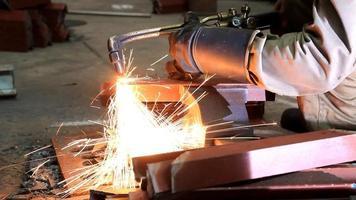 trabajador industrial cortando acero.