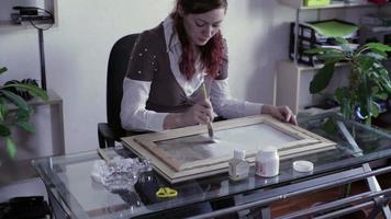 la mujer aplica imprimación sobre lienzo