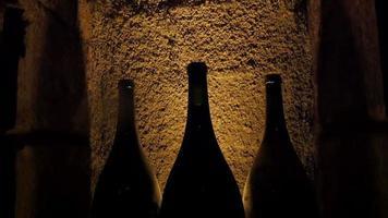 tre bottiglie di vino in piedi sul lato del muro