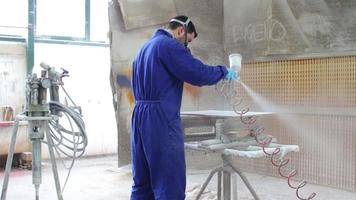 painter in a factory - industrial painting with spray gun - dolly