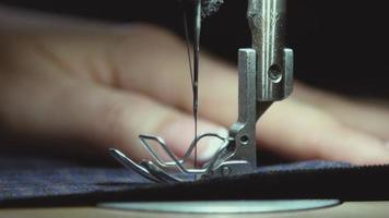 A hand of a dressmaker supporting a cloth while sewing on a machine video