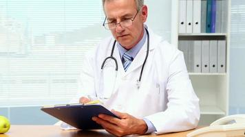 Arzt schreibt in die Zwischenablage an seinem Schreibtisch