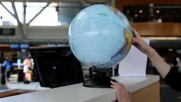 Frau prüft Globuskarte am Informationsschalter
