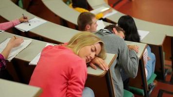 estudiante dormido en el escritorio en la sala de conferencias
