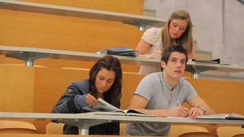 Studenten sitzen an Schreibtischen im Hörsaal