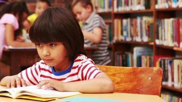 aluno lendo livro na mesa da biblioteca