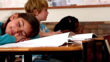 süßes kleines Mädchen, das während des Unterrichts auf dem Schreibtisch schläft