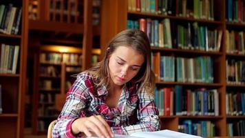 estudante sorridente estudando na mesa da biblioteca