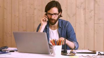 lavoratore occasionale che telefona alla sua scrivania utilizzando il laptop