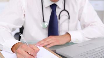médico sério sentado em sua mesa enquanto escreve video