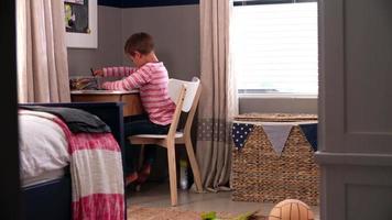 ragazzo seduto alla scrivania in camera da letto a fare i compiti