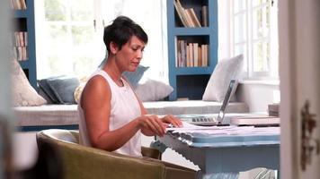 mulher madura trabalhando em um escritório em casa com um laptop video