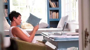 mulher madura na mesa de escritório em casa usando telefone celular