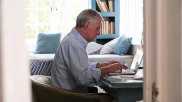 hombre mayor, en el escritorio, trabajo en casa, oficina, con, computadora portátil video