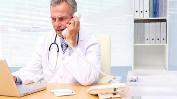 Doctor hablando por teléfono y usando la computadora portátil en su escritorio video