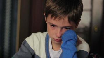 kleiner Junge, der weinend an einem Schreibtisch sitzt und Tränen im Gesicht hat