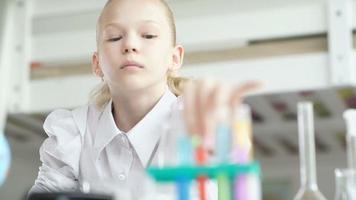 chica haciendo experimento de química. pararse en el escritorio con tubo de ensayo video