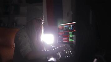 Hacker, programmer working with data code in a dark room. Hackers desk