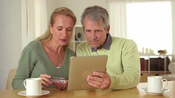 Senior couple using tablet at desk