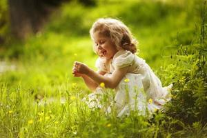 Funny happy little girl with a flower photo