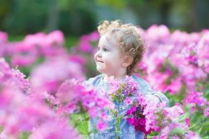 Beautiful curly baby girl playing in garden among pink flowers