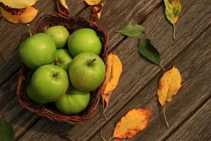 Apple on wooden table with fallen autumn leaves photo