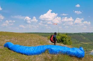 Paraglider prepares to fly over beautiful Bakota reservoir photo