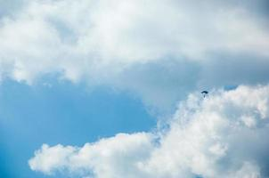 Paratrooper parachuting against white clouds