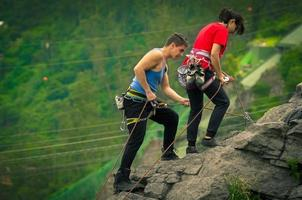 man and woman rapelling down mountain
