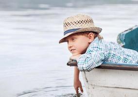 Boy in straw hat lying in old boat photo