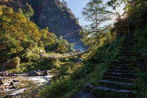 Suspension bridge above mountain canyon river.