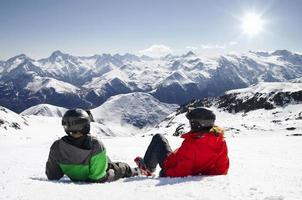 Young happy couple lying in snowy mountains photo