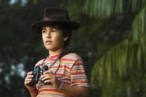 Niño con sombrero de aventurero mirando con binoculares.