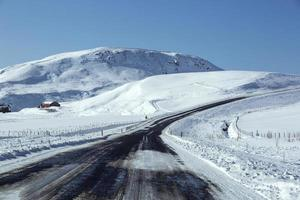 Snowy and slippery road with volcanic mountains in wintertime