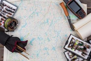 fly-fishing tackles on paper map background photo