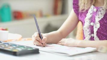 petite fille dessine un crayon bleu. fille assise à un bureau et dessine