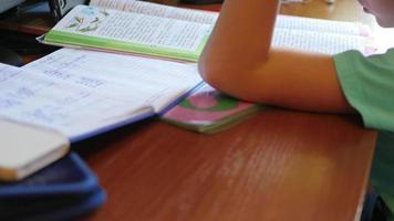 bambino che fa i compiti, leggendo un libro a tavola