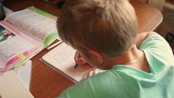 il bambino fa i compiti, scrive in un quaderno a tavola