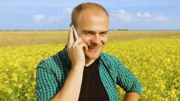jovem falando em um telefone celular em um campo