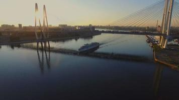 un barco pasa por debajo del puente atirantado