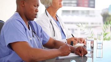 médicos sérios escrevendo em seus blocos de notas