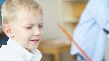 retrato de un chico lindo con cabello rubio. niño dibuja con pinturas video