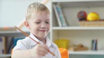 carino bambino 5-7 anni sta disegnando e usando acquarello