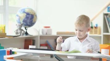 interno della stanza di un bambino. un ragazzo che tiene un pennello per dipingere