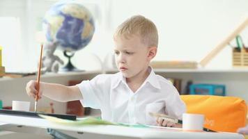 ragazzo carino in età scolare dipinge acquerelli. ragazzo di 5-7 anni