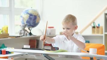 il bambino è impegnato nella creatività. ragazzo dipinto con acquerelli