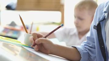 due ragazzi disegnano diligentemente. amicizia dei bambini