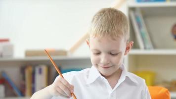 o menino de cabelos loiros pinta aquarelas. menino enterrado escova de dor