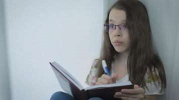 Niña seria con gafas hace diligentemente sus deberes en la ventana